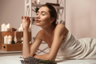 Image of amazing young beautiful woman lies in bathroom over candles smell lavender.
