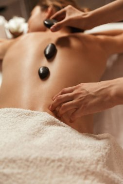 Top view of a woman having hot stone massage in spa welness center