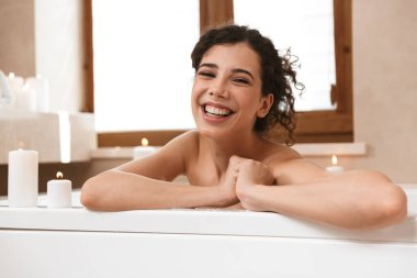 Image of young cute pretty woman in bathroom lies resting in bath.