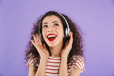 Portrait of a happy young casual woman listening to music with headpones isolated