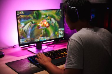 Photo of teenage gamer boy playing video games on computer in dark room wearing headphones and using backlit colorful keyboard stock vector