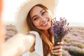 Lovely young girl in straw hat holding lavender bouquet at the field, taking a selfie
