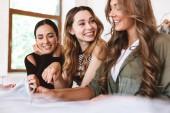 Tři usmívající se mladé ženy oblečení návrháři pracují společně v ateliéru, u stolu