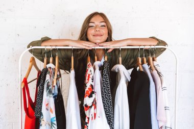 Pretty young woman clothes designer standing at the clothes rack indoors