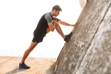 Profile photo of athletic sportsman 20s in t-shirt listening to music via wireless headphones and stretching legs near concrete wall at seaside
