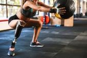 Porträt der schönen invaliden Frau mit Prothese im Trainingsanzug beim Sit-Ups mit Fitnessball im Fitnessstudio