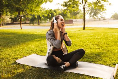 image of relaxed european woman 20s in sportswear listening to music and singing while sitting on exercise mat in green park