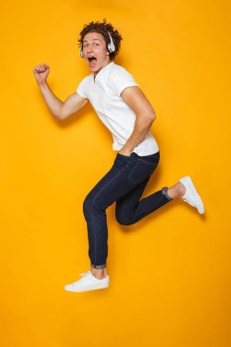 Full length photo of young excited guy with curly hair running or jumping while listening to music via headphones isolated over yellow background