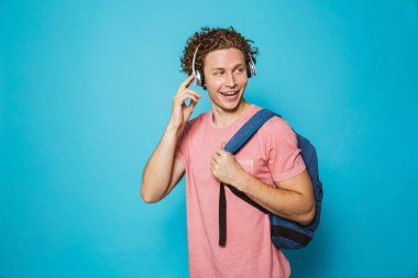 Portrait of attractive man 18-20 with curly hair wearing backpack listening to music via headphones isolated over blue background