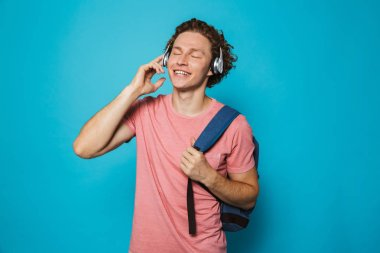 Photo of european college man 18-20 with curly hair wearing backpack listening to music via headphones isolated over blue background