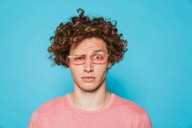 Portrait of a confused curly haired man looking at camera isolated over blue background stock vector