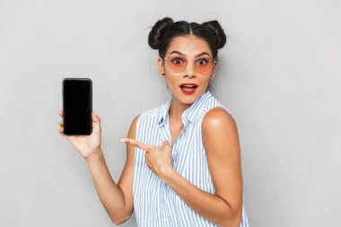 Portrait of an excited young woman in sunglasses isolated, showing blank screen mobile phone