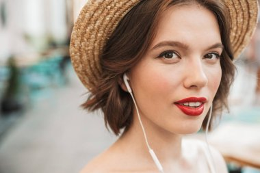 Close up image of Pretty smiling woman in dress and straw hat listening music while looking at the camera outdoors