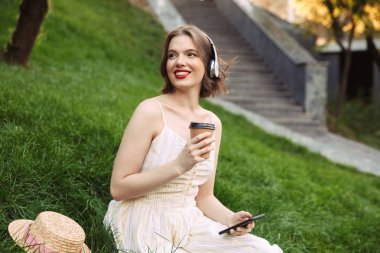 Happy woman in dress and headphones drinking coffee and listening music while sitting in park