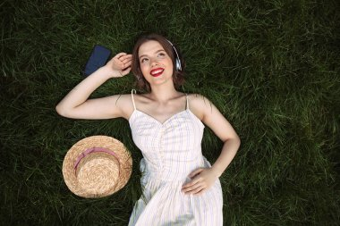 Top view of happy woman in dress and headphones lying on grass while listening music and looking away outdoors