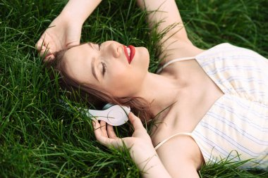 Pleased woman in dress and headphones lying on grass with closed eyes while listening music outdoors