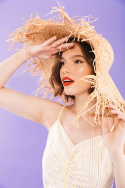 Close up portrait of a pretty young woman dressed in dress and straw hat looking away over violet background