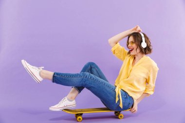 Portrait of a happy young girl in headphones sitting on skateboard isolated over violet background