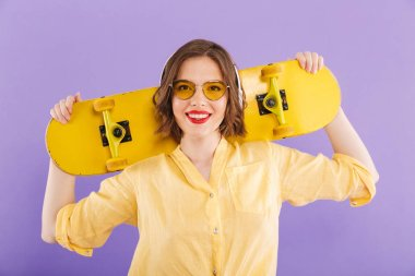 Portrait of a cheerful young girl in headphones holding skateboard,standing isolated over violet background