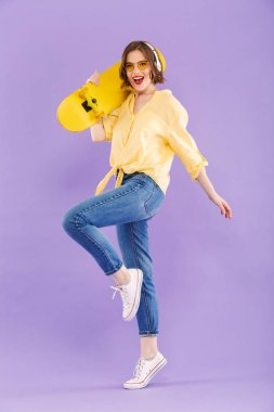 Full length portrait of an excited young girl in headphones holding skateboard,standing isolated over violet background