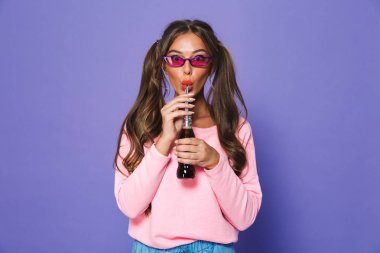 Portrait of a lovely girl in sunglasses drinking fizzy drink with a straw isolated over violet background