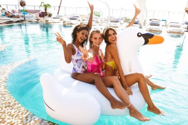 Three cheerful young women in swimwear swimming together at the swimming pool outdoors with inflatable ring