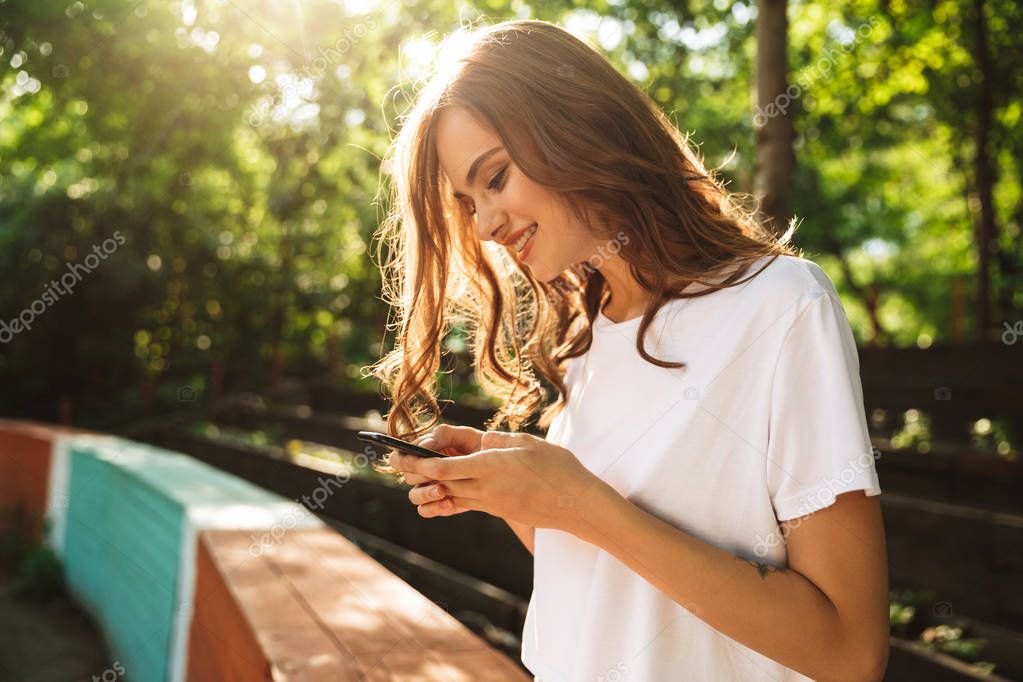 Attractive young girl using mobile phone at the park outdoors