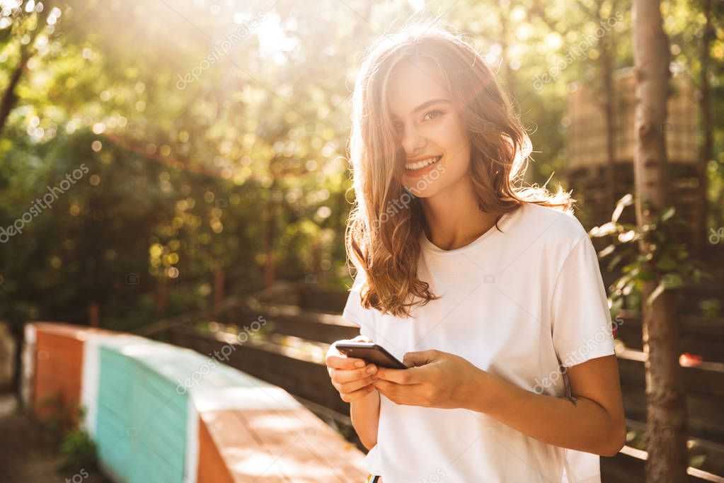 Cheerful young girl using mobile phone at the park outdoors