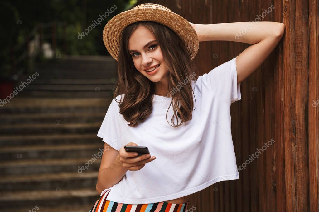 Smiling young girl holding mobile phone while standing at the wooden background outdoors