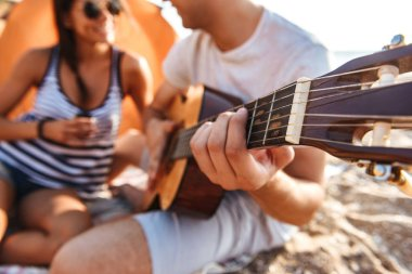 Photo of happy friends loving couple outdoors on the beach sitting while play on the guitar.