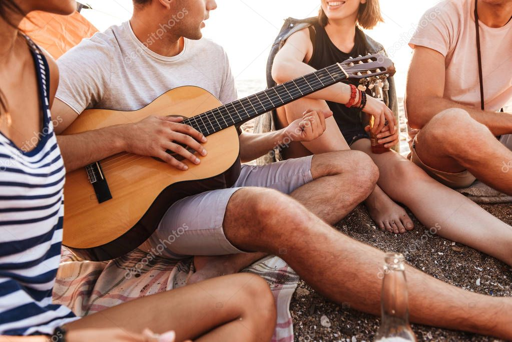 Cropped image of a group of cheerful young friends having fun time together at the beach, drinking beer, playing guitar while camping