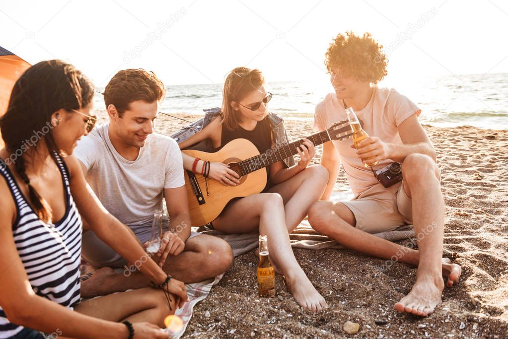 Group of positive young friends having fun time together at the beach, drinking beer, playing guitar while camping