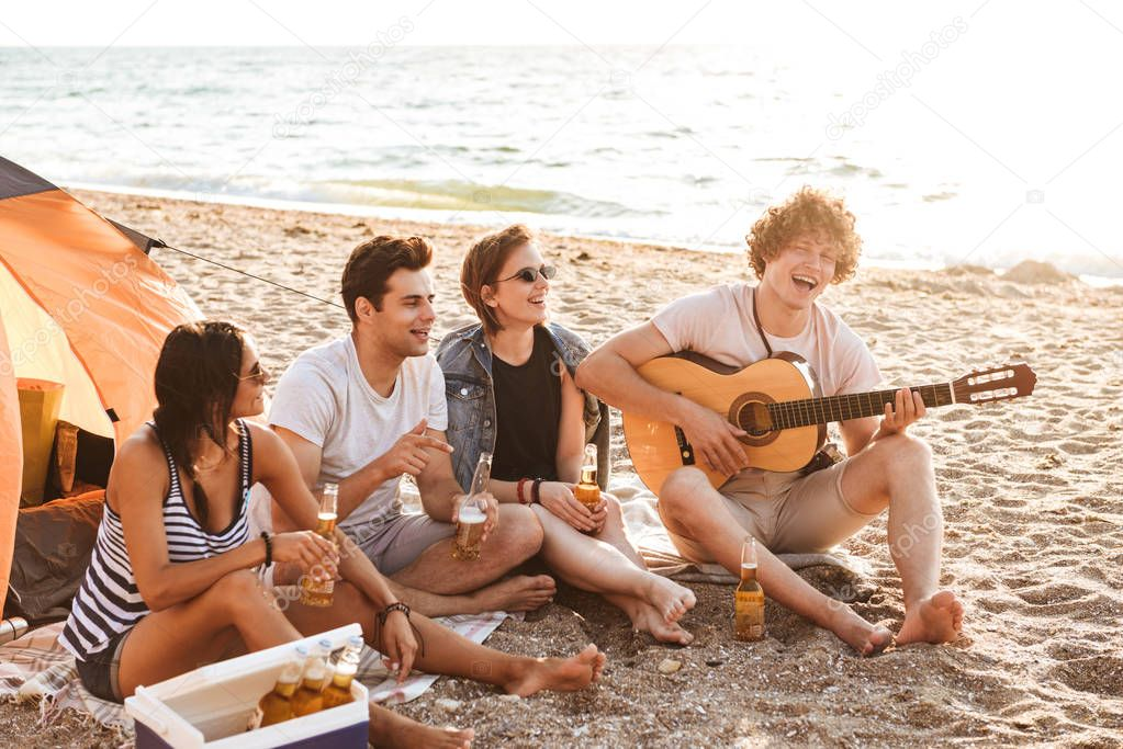 Group of excited young friends having fun time together at the beach, drinking beer, playing guitar while camping