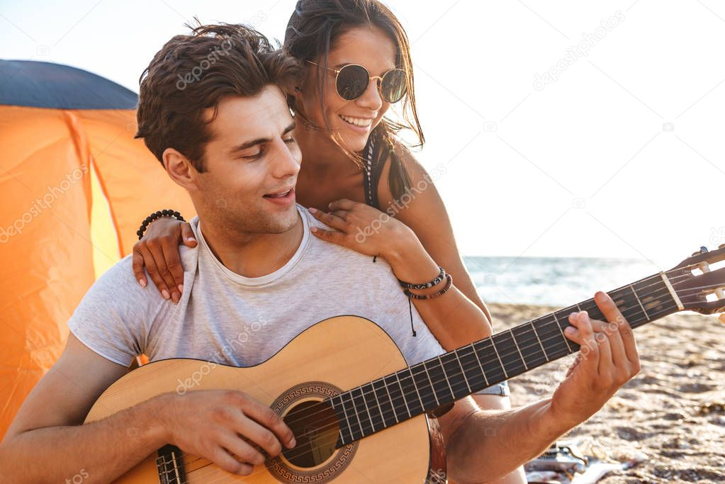 Image of cute friends loving couple outdoors on the beach sitting while play on the guitar.