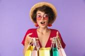 Fotografie Obrázek bruneta žena vzrušená 20s v slaměný klobouk drží barevné papírové nákupní tašky izolované fialové pozadí