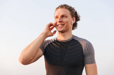 Smiling young sportsman in wireless earphones standing outdoors over blue sky