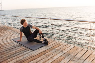 Portrait of a handsome sportsman sitting on a fitness mat the beach, listening to music with earphones