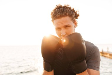 Photo of young handsome sports man boxer outdoors on the beach boxing in gloves.