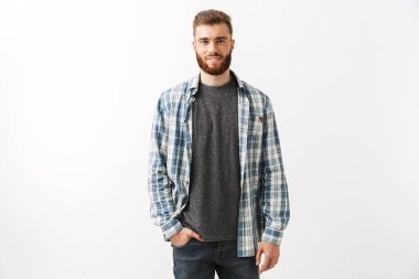 Portrait of a handsome young bearded man looking at camera isolated over white