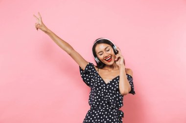 Happy brunette woman in dress and headphones listening music while showing peace gesture and enjoys over pink background