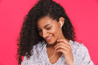 Portrait of a smiling young african woman in summer dress standing isolated over pink background, listening to music with earphones