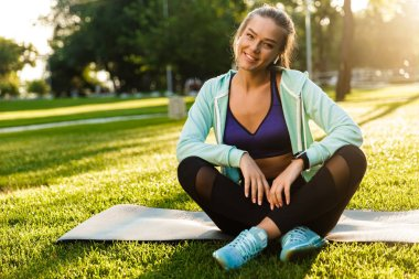 Photo of amazing smiling young sports woman in park outdoors listening music.