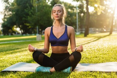 Photo of amazing concentrated young sports woman in park outdoors meditate.