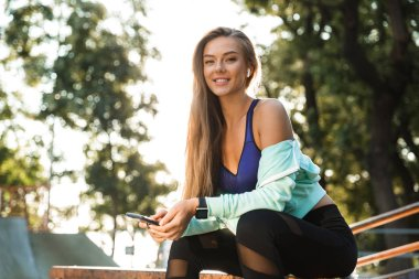 Photo of pretty young sports woman in park outdoors listening music with earphones using mobile phone.