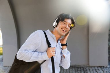 Joyful business man dressed in shirt carrying backpack at the city street, listening to music with headphones
