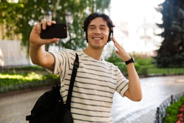 Cheerful casual man carrying backpack at the city street, listening to music with headphones, taking a selfie
