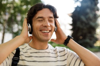 Happy casual man carrying backpack at the city street, listening to music with headphones