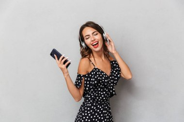 Portrait of a joyful young girl in dress over gray background, listening to music with headphones