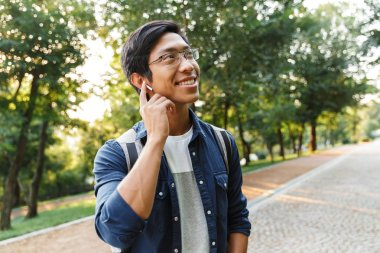 Smiling asian male student in eyeglasses and earphones listening music while looking away