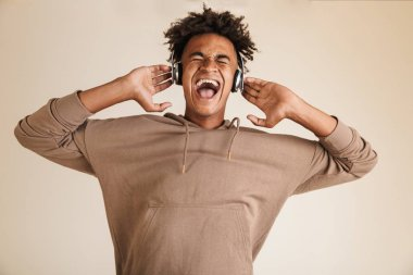 Portrait of a happy young afro american man dressed in hoodie isolated, listening to music with headphones, screaming